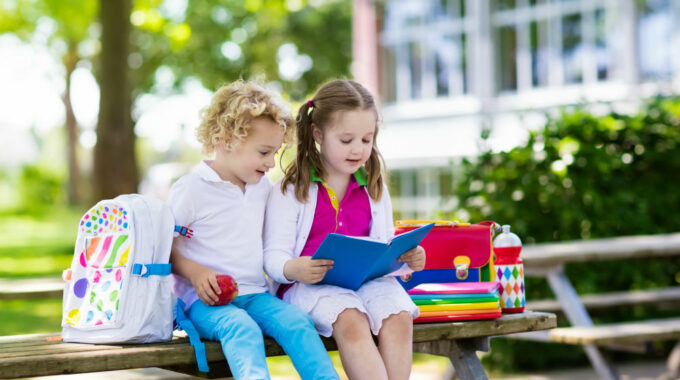 Back-to-school-park-place-finance-little-girls-books-school-sitting-on-a-bench