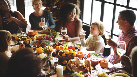 Family-dinner-Thanksgiving-Adults-listening-to-child-with-raised-glasses-where-eat-thanksgiving-texas-park-place-finance