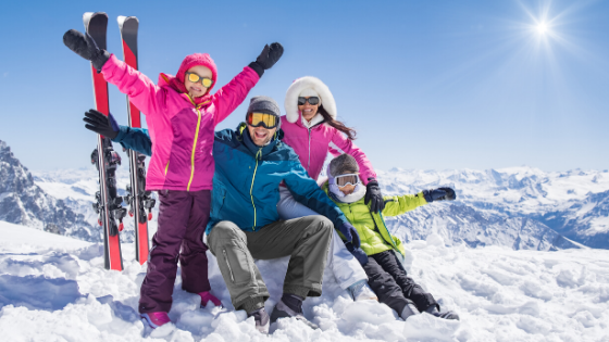 Family-skiing-on-snowy-mountain-at-ski-home