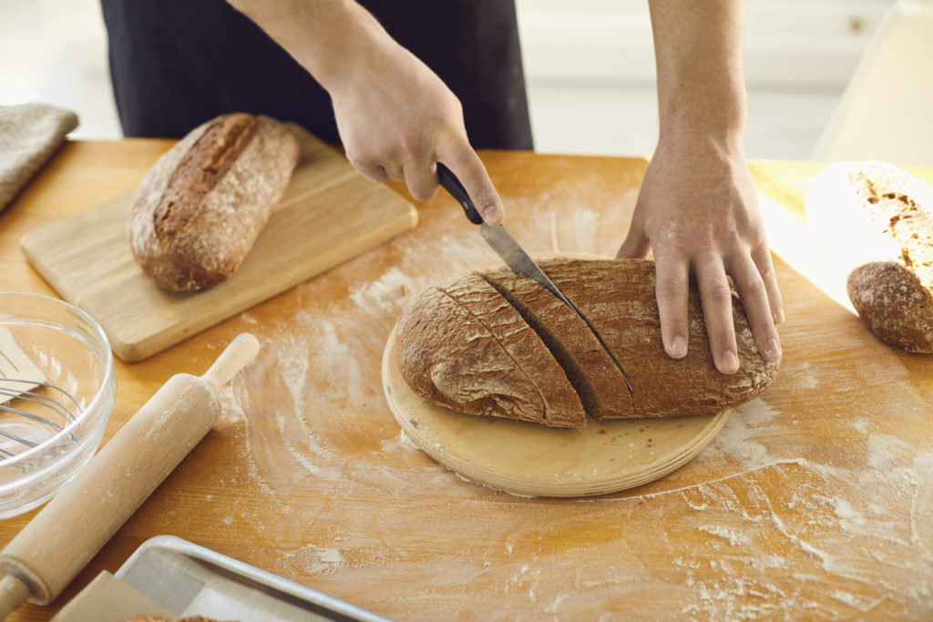 man-cutting-at-home-baked-bread-with-knife