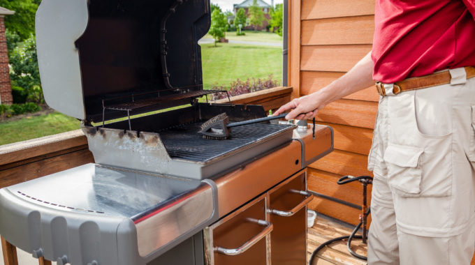 Man-cleaning-grill-summer-maintenance