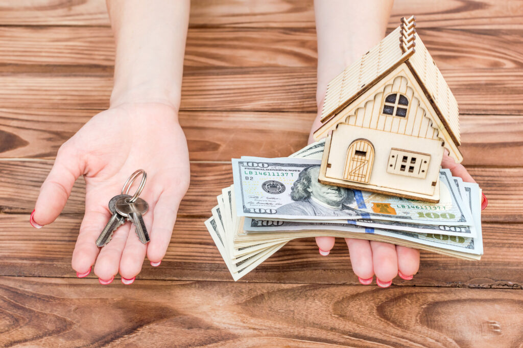 woman-holding-small-house-and-money-and-keys