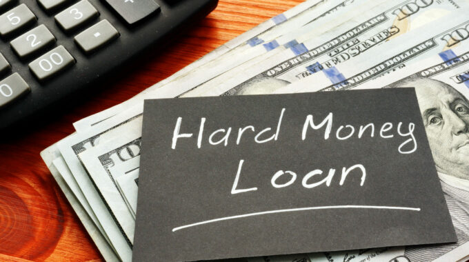 Calculator-and-dollar-bills-on-table-with-sign-hard-money-loan
